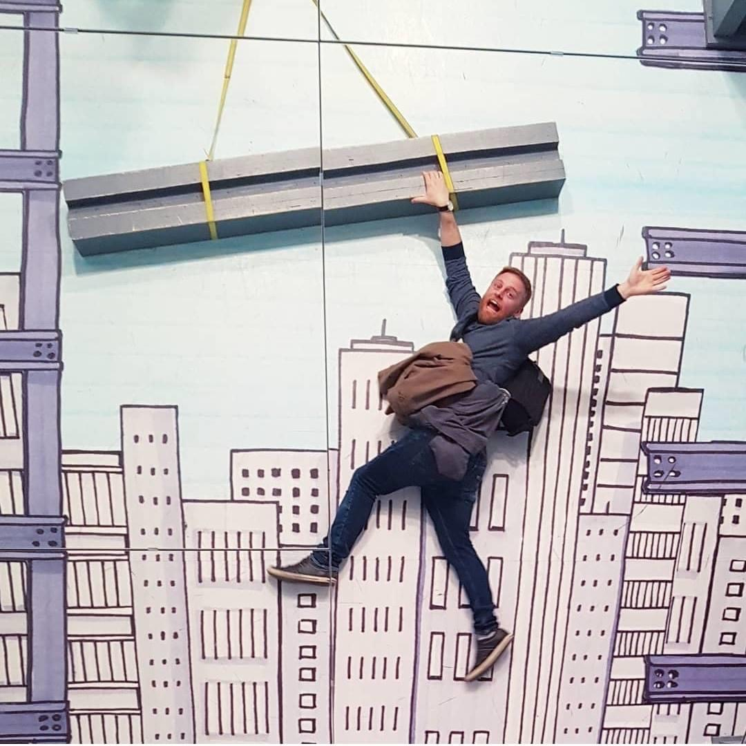 Image background shows high buildings with a girder hanging from an imaginery crane. A man holds on to the girder with one hand, giving the impression of hanging on